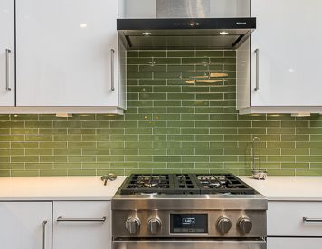 Chinoe Rd Kitchen Remodel, white cabinets, green backsplash, stainless hood and gas range