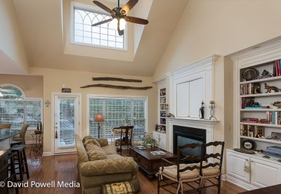 Family room with high vaulted ceiling and a second store window that provides natural lighting.