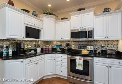 Kitchen has white cabinets, granite counter tops and hardwood floors