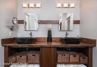 Custom built walnut vanity with double black sinks.