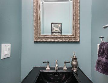 First floor powder room with black pedestal sink.
