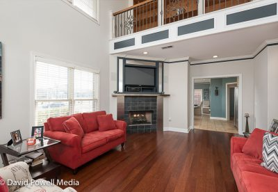 Open two story living room with corner fireplace and hardwood flooring