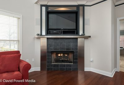 Contemparary corner fireplace with slate tile and stainless steel and mirrored accents.